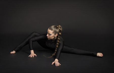 Girl in a black suit with long hair, performs gymnastic exercises. Studio shot on dark background.