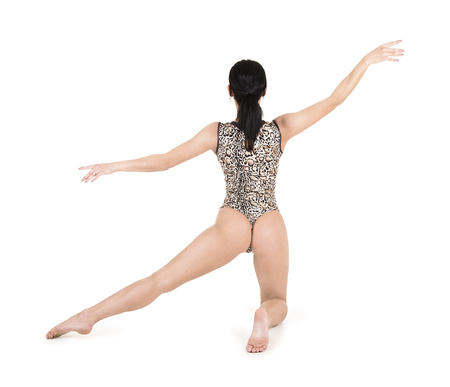 A young woman in a leopard swimsuit engaged in fitness, acrobatics and yoga. Studio shot on white background. Isolated image. Stockfoto