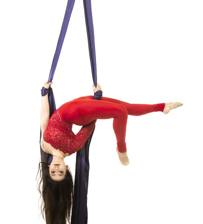 A young girl with long hair in a red suit performs gymnastic and circus exercises on silk. Studio shooting on white background, isolated image.