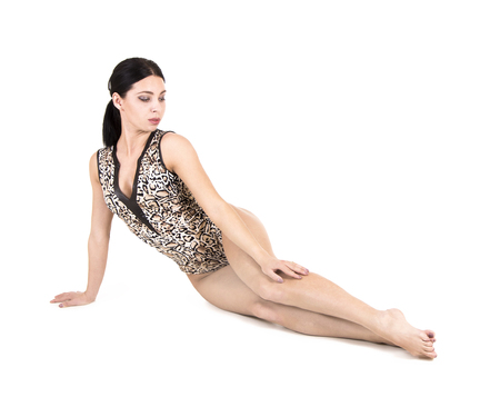 A young woman in a leopard swimsuit engaged in fitness, acrobatics and yoga. Studio shot on white background. Isolated image. 版權商用圖片