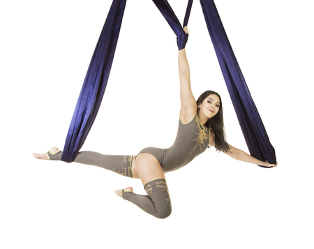 Young, smiling acrobat, with long hair, in a gray suit and leggings doing exercises on blue airy silk . Studio shooting on white background.