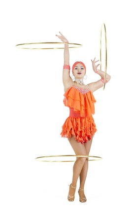 A girl in a stage dress performs a dance with a hula Hoop. Studio shooting on a dark background.