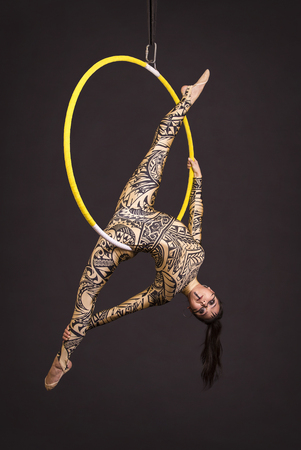A young girl in a suit with a print performs acrobatic elements in the air ring. Studio shooting performances on a black background.