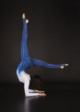 Girl acrobat, gymnastics, a young athlete in a blue and white suit , practicing acrobatics. Isolated images on white background. Stock Photo