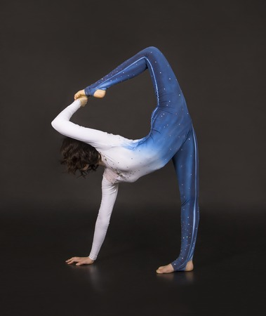 Girl acrobat, gymnastics, a young athlete in a blue and white suit , practicing acrobatics. Isolated images on dark background. Imagens