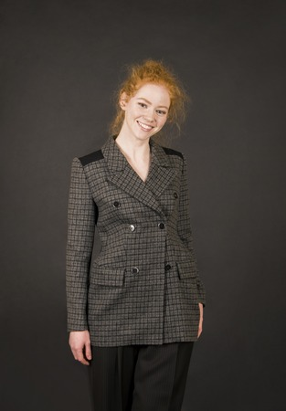 A girl in a jacket and dark pants posing. Studio shooting on a dark background.