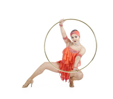 A girl in a stage dress performs a dance with a hula Hoop. Studio shooting on a white background.