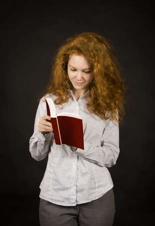 Emotional,red-haired girl in a light shirt with a book. Studio shooting on a dark background.