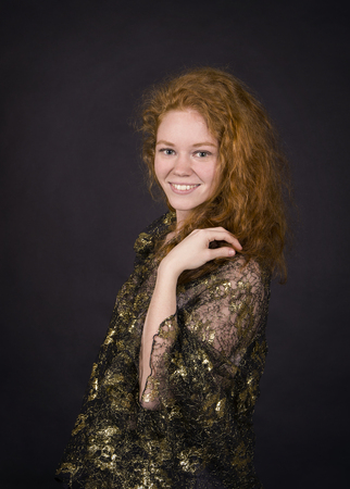 Emotional, red-haired girl in a brocade blouse posing. Studio shooting on a dark background.