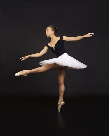 Gorgeous ballerina in a white tutu dancing ballet. Studio shooting on a dark background , isolated images. Zdjęcie Seryjne
