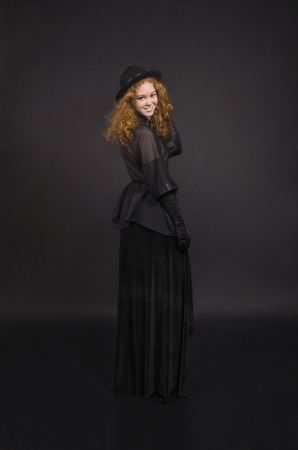 Emotional,red-haired girl in a black skirt,black blouse, black hat and black gloves. Studio shooting on a dark background. Stock Photo - 122824638