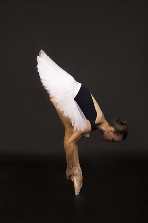 Gorgeous ballerina in a white tutu dancing ballet. Studio shooting on a dark background, isolated images.