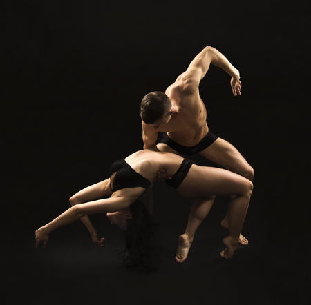 A young girl performing acrobatic dance and stunts.Studio shooting on a dark background.