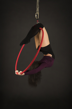 A girl in a dark suit and leggings performs acrobatic elements on the air ring. Studio shooting performances on a black background.