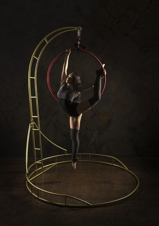 Gorgeous girl, aerial acrobat, in a dark suit performs acrobatic elements on a portable air ring, in the stage light. Studio shooting performances on a dark background.