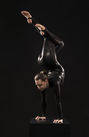 Eine charmante Turnerin im schwarzen Anzug, die sich im Licht des Kontras mit Akrobatik beschäftigt. Isolierte Bilder auf dunklem Hintergrund.