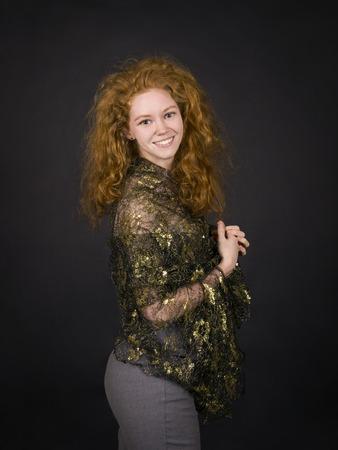 Emocional, chica pelirroja en una blusa de brocado posando. Estudio de rodaje sobre un fondo oscuro.