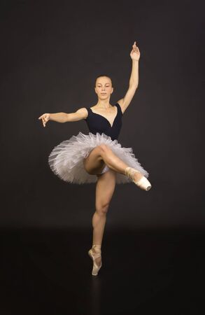 Gorgeous ballerina in a white tutu dancing ballet. Studio shooting on a dark background , isolated images. Фото со стока