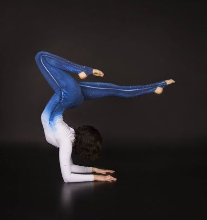 Girl acrobat, gymnastics, a young athlete in a blue and white suit , practicing acrobatics. Isolated images on dark background.