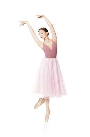 Elegant girl in a pink skirt and beige top dancing ballet. Studio shooting on white background, isolated images. Stock Photo