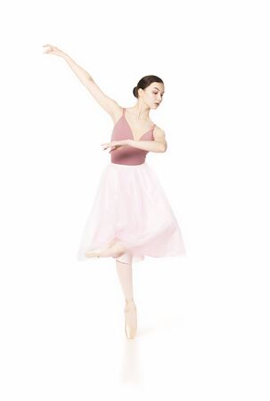 Elegant girl in a pink skirt and beige top dancing ballet. Studio shooting on white background, isolated images. Stok Fotoğraf