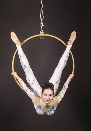 A slender,dark-haired girl - an air acrobat in a white and blue suit, performs exercises in an air ring. Studio shooting on a dark background. Stok Fotoğraf