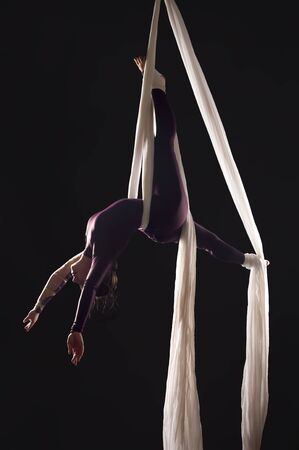 Sporty girl in a burgundy suit performs gymnastic and circus exercises on white silk, in the contra light. Studio shooting on a dark background, isolated images.