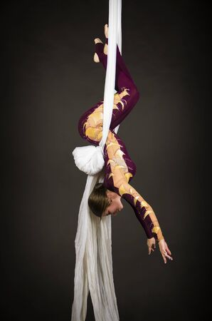 Sporty girl in a burgundy suit performs gymnastic and circus exercises on white silk. Studio shooting on a dark background, isolated images.