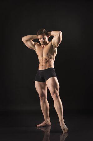 Hombre atlético fuerte muestra cuerpo musculoso. Estudio de rodaje sobre un fondo oscuro.