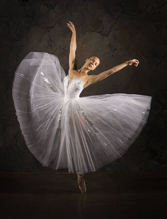 Slender girl in a white corset tutu dancing ballet. Studio shooting on a dark background, isolated images. 免版税图像