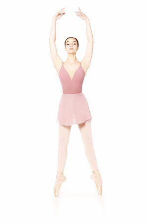 Elegant girl in a pink skirt and beige top dancing ballet. Studio shooting on white background, isolated images. Foto de archivo