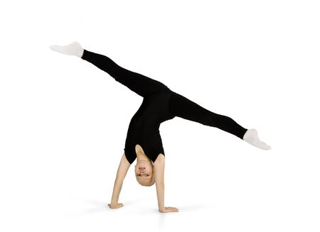 A little girl in a black gymnastic suit performs gymnastic exercises on a white background. Studio shooting, isolated image.