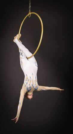 A slender,dark-haired girl - an air acrobat in a white and blue suit, performs exercises in an air ring. Studio shooting on a dark background. Imagens
