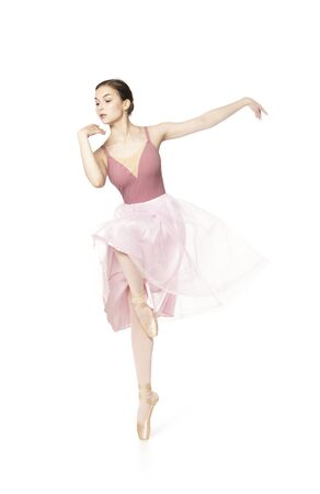 Elegant girl in a pink skirt and beige top dancing ballet. Studio shooting on white background, isolated images. 写真素材