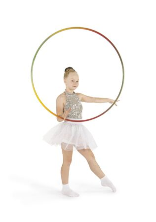 A little girl in a light stage costume performs gymnastic exercises on a white background. Studio shooting, isolated image.