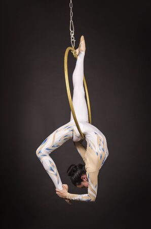 A slender,dark-haired girl - an air acrobat in a white and blue suit, performs exercises in an air ring. Studio shooting on a dark background. Zdjęcie Seryjne