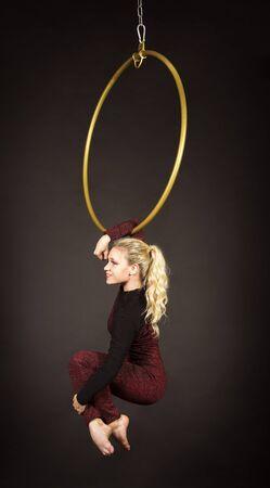 Een slank blond meisje, een luchtacrobaat in een rood pak met lang haar, voert oefeningen uit in een luchtring. Studio-opnamen op een donkere achtergrond.