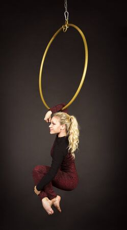 Una chica rubia esbelta, una acróbata aérea con un traje rojo y cabello largo, realiza ejercicios en un anillo de aire. Estudio de rodaje sobre un fondo oscuro.