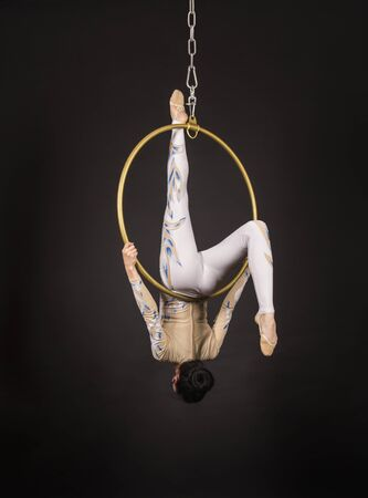 A slender,dark-haired girl - an air acrobat in a white and blue suit, performs exercises in an air ring. Studio shooting on a dark background. Stock Photo