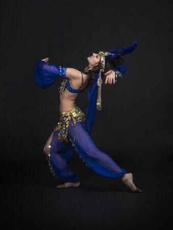 Junges, lächelndes Mädchen, das den östlichen Tanz tanzt. Bauchtanz-Bühnenaufführung. Aufnahmen im Studio auf dunklem Hintergrund.