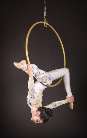 Una chica delgada de cabello oscuro, una acróbata aérea con un traje blanco y azul, realiza ejercicios en un anillo de aire. Estudio de rodaje sobre un fondo oscuro. Foto de archivo