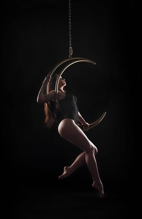The girl, an aerial acrobat, performs on a sports equipment of the