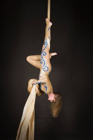 A slender girl in a beige suit performs gymnastic and circus exercises on Golden silk. Studio shooting on a dark background, isolated images. Imagens