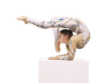 Acrobat doing gymnastics, a young circus artist in a white and blue suit, performs acrobatic elements. Studio shooting isolated image on white background. Stock Photo