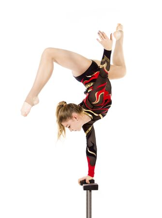 Beautiful equilibrist in a red and black suit, performs exercises on acrobatic canes. Studio photo on white background, isolated images.