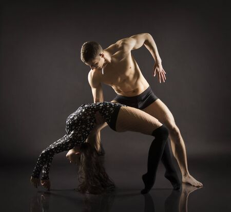 A young girl and young man performing acrobatic dance and stunts.Studio shooting on a dark background.
