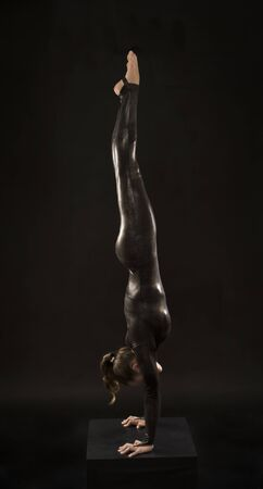 A charming girl gymnast, in a black suit, engaged in acrobatics in the light of the contra. Isolated images on a dark background.
