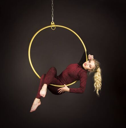 A slender blonde girl-an air acrobat in a red suit with long hair , performs exercises in an air ring. Studio shooting on a dark background.