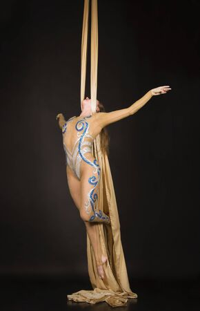 A slender girl in a beige suit performs gymnastic and circus exercises on Golden silk. Studio shooting on a dark background, isolated images.