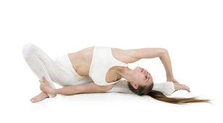 A young woman in a white suit performs acrobatic elements and yoga. Studio shot on white background. Isolated image.